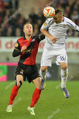 Fiorentina's forward Jasmin Kurtic jumps for a header with Guingamp's Lars Jacobsen, left, during their Europa League Group K soccer match in Guingamp, western France, . Fiorentina win 1-2