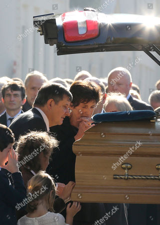 Bernadette de Margerie, widow of former Total SA Chief Executive Christophe de Margerie, reacts at her husband's coffin, comforted by Elysee Palace secretary general Jean-Pierre Jouyet, after the funeral service at Saint Sulpice church in Paris, France, . Margerie and three French crew members were killed Oct. 20, when the business jet they were in clipped an airport snowplow on takeoff at Moscow's Vnukovo airport, crashed and burst into flames