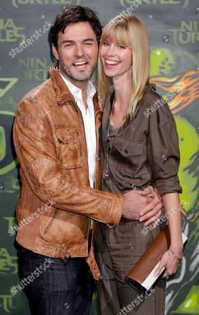 German Tenor Tobey Wilson, left, and model Sabrina Gehrmann, right, pose for the photographers as they arrives for the screening of the movie 'Teenage Mutant Ninja Turtles' in Berlin, Germany
