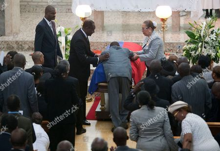 "A man leans on the coffin during the funeral ceremony for Haiti's late Dictator Jean-Claude ""Baby Doc"" Duvalier in Port-au-Prince, Haiti, . Many had wondered whether the self-proclaimed ""president for life"" would receive a state funeral following his death last Saturday from a heart attack at age 63, but Duvalier's attorney announced late this week that friends and family would arrange a simple and private funeral"