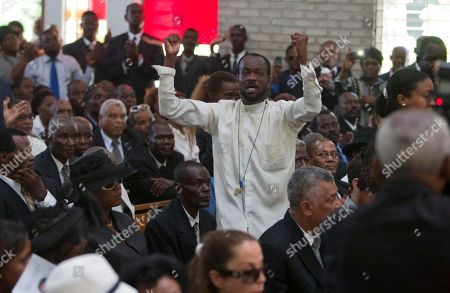 "A man yells ""Long live Duvalier! He's not dead!"" during the funeral ceremony for Haiti's late Dictator Jean-Claude ""Baby Doc"" Duvalier in Port-au-Prince, Haiti, . Hundreds of people attended the funeral, displaying respect for a man who was widely reviled for repression and corruption during his 15 years in power"