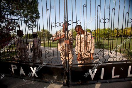 "National police officers lock the gate of the private Morgue Pax Villa where the body of Former Haitian dictator Jean-Claude Duvalier, known as ""Baby Doc,"" is kept, in Port-au-Prince, Haiti, . Duvalier, the self-proclaimed ""president for life"" of Haiti whose corrupt and brutal regime sparked a popular uprising that sent him into a 25-year exile, died Saturday of a heart attack, his attorney said"