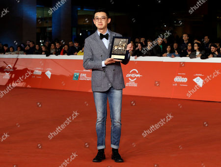 Stock Image of Director Xu Ang poses for photographers with the Cinema D'Oggi (Today's Filmography) award trophy for the movie 'Shier Gongmin' (12 Citizens) during the 9th edition of the Rome Film Festival in Rome