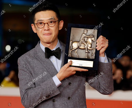 Stock Photo of Director Xu Ang poses for photographers with the Cinema D'Oggi (Today's Filmography) award trophy for the movie 'Shier Gongmin' (12 Citizens) during the 9th edition of the Rome Film Festival in Rome