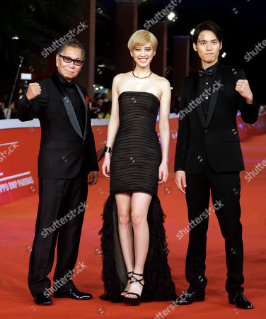 """From right, Actors Hirona Yamazaki, Sota Fukushi, and Director Takashi Miike pose for photographers as they arrive on the red carpet for the screening of the movie """"As the Gods Will"""" at the Rome Film Festival, in Rome"""