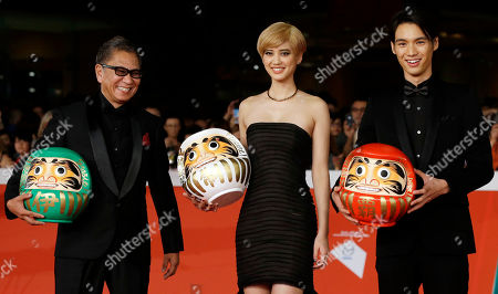 """From right, Actors Hirona Yamazaki, Sota Fukushi, and Director Takashi Miike pose for photographers as they arrive on th red carpet for the screening the movie """"As the Gods Will"""" at the Rome Film Festival, in Rome"""