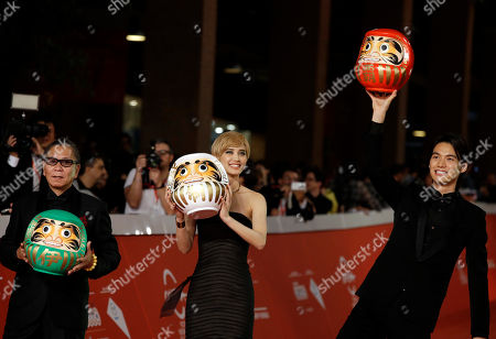 """From right, Actors Hirona Yamazaki, Sota Fukushi, and Director Takashi Miike pose for photographers as they arrive on the red carpet for the screening the movie """"As the Gods Will"""" at the Rome Film Festival, in Rome"""