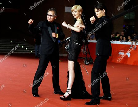 From right, Actors Hirona Yamazaki, Sota Fukushi, and Director Takashi Miike pose for photographers as they arrive on the red carpet for the screening of the movie As the Gods Will at the Rome Film Festival, in Rome