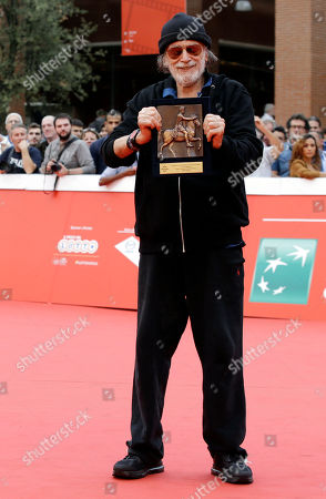 Tomas Milian Actor Tomas Milian holds the Marco Aurelio Acting Award as he poses for the photographers on the red carpet at the Rome Film Festival, in Rome