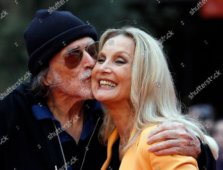 Actor Tomas Millan kisses Barbara Bouchet as they pose for the photographers on the red carpet at the Rome Film Festival, in Rome
