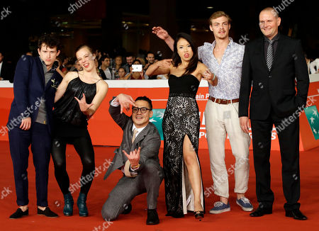 "From left, actor and actresses Joel Basman, Saskia Rosendahl, Trang Le Hong, director Burhan Qurbani, actors david schuette and Devid Striesow pose for photographers as they arrive on the red carpet for the movie ""We are young. We are strong."" at the Rome Film Festival, in Rome"