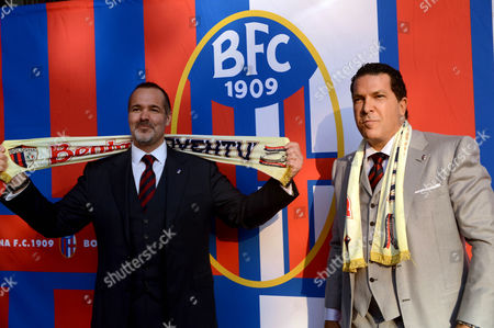 Joe Tacopina, right, and Joey Saputo pose in front of the Bologna Football Club logo, in Bologna, Italy, . A group of North Americans led by New York lawyer Joe Tacopina were presented Thursday as the new owners of Italy's cash-strapped Serie B soccer club Bologna. Tacopina was named club president and Montreal Impact president Joey Saputo is a large investor. Tacopina, who represents New York Yankees slugger Alex Rodriguez in his drug case, resigned from his position on Roma's board to pursue the Bologna deal