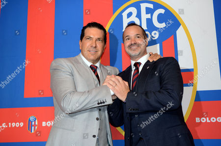"Joe Tacopina, right, and Joey Saputo pose in front of the Bologna Football Club logo, in Bologna, Italy. New Bologna owners Joe Tacopina and Joey Saputo have issued a joint statement on the club's website reassuring fans that they are still collaborating amid reports of a rift. They say, ""From the start we have been partners and friends and that hasn't changed. ... We will try to assure adequate financial resources for the club for many years."" New York lawyer Tacopina and Montreal Impact president Saputo purchased Bologna in October"