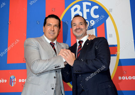 Joe Tacopina, right, and Joey Saputo pose in front of the Bologna Football Club logo, in Bologna, Italy. New York lawyer Joe Tacopina has resigned as Bologna president following a rift with Canadian investor Joey Saputo, clearing the way for Saputo, already president of MLS club Montreal Impact, to also become Bologna's president