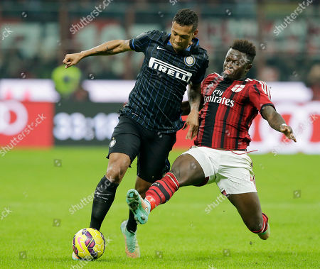 Inter Milan's Fredy Guarin, left, is tackled by AC Milan's Sulley Muntari during the Serie A soccer match between AC Milan and Inter Milan at the San Siro stadium in Milan, Italy