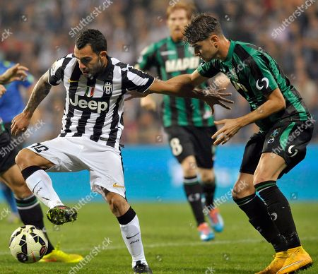 Sassuolo's Luca Antei, right, vies for the ball with Juventus' Carlos Tevez, during their Serie A soccer match at Reggio Emilia's Mapei stadium, Italy