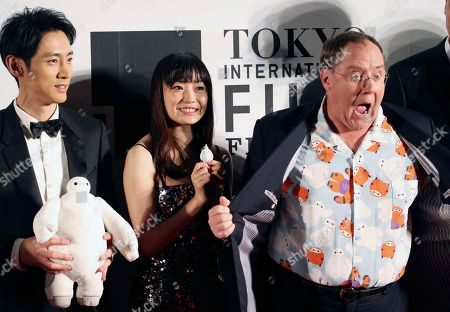 """John Lasetter, Miho Kanno, Kotaro Koizumi John Lasetter, right, chief creative officer at Pixar, Walt Disney Aniamation Studios and Disney Toon Studios, poses for a photo with Japanese actors, Miho Kanno, center, and Kotaro Koizumi, both holding a character of """"Baymax,"""" the inflatable marshmallow-like robot in the animation movie """"Big Hero 6,"""" during an opening ceremony of the 27th Tokyo International Film Festival in Tokyo. Disney executives call their next film """"a love letter to Japanese culture."""" No wonder: This nation can't get enough of animation, especially Disney's"""