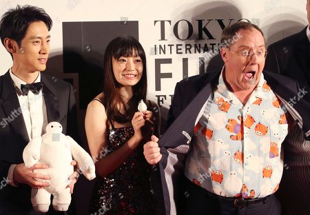 """John Lasetter, Miho Kanno, Kotaro Koizumi John Lasetter, right, chief creative officer at Pixar, Walt Disney Aniamation Studios, and Disney Toon Studios, poses for a photo with Japanese actors, Miho Kanno, center, and Kotaro Koizumi, both holding a character of """"Baymax,"""" the inflatable marshmallow-like robot in the animation film """"Big Hero 6,"""" during an opening ceremony of the 27th Tokyo International Film Festival in Tokyo"""