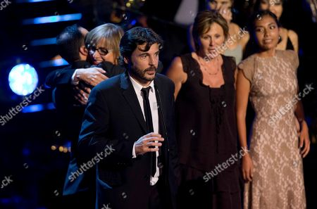"Diego Quemada-Diez Spanish born director Diego Quemada-Diez, left, gives his acceptance speech after receiving the Fenix Award for best film, ""La Jaula de Oro"" during the Fenix Iberoamerican Film Awards at the Esperanza Iris Theater in Mexico City"