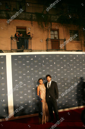 Guatemalan actress Karen Martinez and Spanish director Diego Quemada-Diez pose for photographers during their red carpet walk during the Fenix Iberoamerican Film awards at the Esperanza Iris Theater in Mexico City