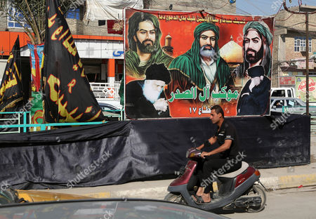 In this picture, a motorcycle passes by banners of religious leaders of Shiites in Ghadeer district in southeastern Baghdad, Iraq. Religious banners and portraits of Imam Hussein, a grandson of the Prophet Muhammad, hang from homes, bridges, stores and even colleges across much of Baghdad and can be seen even in Sunni-majority areas. They also adorn government buildings and hundreds of security checkpoints across the city, reinforcing Sunni fears that Shiite Prime Minister Haider al-Abadi is no less sectarian than his predecessor Nouri al-Maliki, whose policies were widely seen as aggravating Sunni grievances