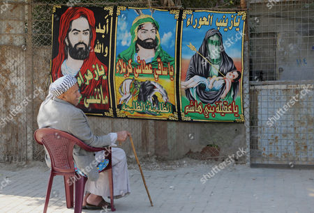 A man sits near Shiite banners hanging on a fence in Ghadeer district in southeastern Baghdad, Iraq. Religious banners and portraits of Imam Hussein, a grandson of the Prophet Muhammad, hang from homes, bridges, stores and even colleges across much of Baghdad and can be seen even in Sunni-majority areas. They also adorn government buildings and hundreds of security checkpoints across the city, reinforcing Sunni fears that Shiite Prime Minister Haider al-Abadi is no less sectarian than his predecessor Nouri al-Maliki, whose policies were widely seen as aggravating Sunni grievances