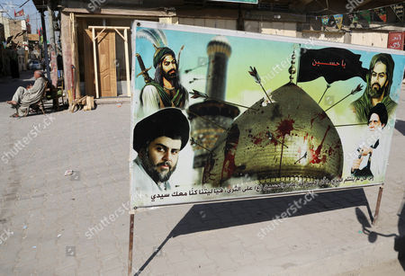 """A banner with pictures of Shiite leaders are seen in Sadr City, Baghdad, Iraq. The Arabic on the banner reads, """"O Hussein, Until now, the wounds are not healed, as if the past has come back. Hussein's blood is on the ground. We wish we were with you."""" Religious banners and portraits of Imam Hussein, a grandson of the Prophet Muhammad, hang from homes, bridges, stores and even colleges across much of Baghdad and can be seen even in Sunni-majority areas. They also adorn government buildings and hundreds of security checkpoints across the city, reinforcing Sunni fears that Shiite Prime Minister Haider al-Abadi is no less sectarian than his predecessor Nouri al-Maliki, whose policies were widely seen as aggravating Sunni grievances"""