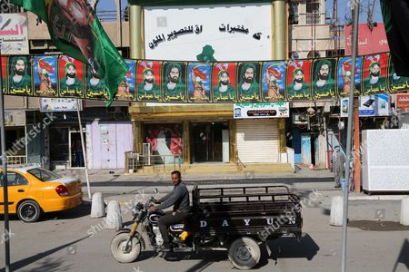 A motorcycle passes by banners of religious leaders of Shiites in Sadr City Baghdad, Iraq. Religious banners and portraits of Imam Hussein, a grandson of the Prophet Muhammad, hang from homes, bridges, stores and even colleges across much of Baghdad and can be seen even in Sunni-majority areas. They also adorn government buildings and hundreds of security checkpoints across the city, reinforcing Sunni fears that Shiite Prime Minister Haider al-Abadi is no less sectarian than his predecessor Nouri al-Maliki, whose policies were widely seen as aggravating Sunni grievances