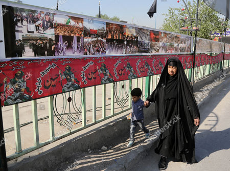 A woman and a child pass by banners with pictures of Shiite-related events in Ghadeer district in southeastern Baghdad, Iraq. Religious banners and portraits of Imam Hussein, a grandson of the Prophet Muhammad, hang from homes, bridges, stores and even colleges across much of Baghdad and can be seen even in Sunni-majority areas. They also adorn government buildings and hundreds of security checkpoints across the city, reinforcing Sunni fears that Shiite Prime Minister Haider al-Abadi is no less sectarian than his predecessor Nouri al-Maliki, whose policies were widely seen as aggravating Sunni grievances