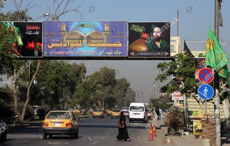 People pass under Shiite banners in Ghadeer district in southeastern Baghdad, Iraq. Religious banners and portraits of Imam Hussein, a grandson of the Prophet Muhammad, hang from homes, bridges, stores and even colleges across much of Baghdad and can be seen even in Sunni-majority areas. They also adorn government buildings and hundreds of security checkpoints across the city, reinforcing Sunni fears that Shiite Prime Minister Haider al-Abadi is no less sectarian than his predecessor Nouri al-Maliki, whose policies were widely seen as aggravating Sunni grievances