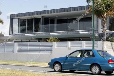 A security guard drives past Phil Rudd's waterfront home in Tauranga, New Zealand. The AC/DC drummer faces serious charges and remains secluded in a quiet town that had seemed to accept him and his excesses