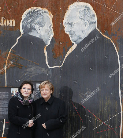 """Angela Merkel, Ewa Kopacz Poland's Prime Minister Ewa Kopacz,left, and German Chancellor Angela Merkel pose in front of a drawing depicting former Polish Prime Minister Tadeusz Mazowiecki,left,and former German Chancellor Helmut Kohl, during a visit of an exhibition to commemorate 25 years since a symbolic reconciliation between the two neighboring nations whose ties were marked by warfare in Krzyzowa, Poland, . Speaking on the occasion, Merkel stressed that security, freedom and the rule of law are made even more valuable today, when Ukraine's territorial integrity has been violated. """"We are aware that only together with Russia we can assure Europe's long-term security,"""" Merkel said"""
