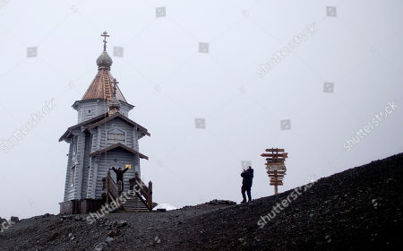 Tourists take pictures at the entrance of the world's southernmost Eastern Orthodox church, the Holy Trinity, located on top of a rocky hill on King George Island, Antarctica. Russian priests here rotate in for yearlong stints, primarily to celebrate Mass for the workers on the Russian Bellinghausen base