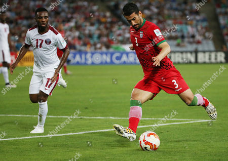 Iran's Ehsan Hajsafi, right, looks to kick the ball as Qatar's Ismail Mohamad looks on during the AFC Asia Cup soccer match between Qatar and Iran in Sydney, Australia