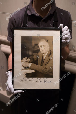 """A member of Sotheby's staff poses with a photograph of U.S. President Franklin D. Roosevelt by Hessler: signed and inscribed """"For Mary, from her friend the other naval person, Franklin D. Roosevelt"""" at the auction house in London, England. It is one lot from a sale of possessions of the late Mary Soames, the last of Winston Churchill's children, due to take place on Dec. 17"""
