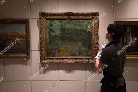 A member of Sotheby's staff prepares to adjust a painting by Winston Churchill called 'The Goldfish Pool at Chartwell' at the auction house in London, England. It is one lot from a sale of possessions of the late Mary Soames, the last of Winston Churchill's children, due to take place on Dec. 17