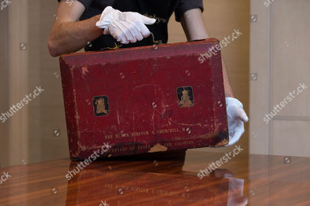 A member of Sotheby's staff poses for a picture with Churchill's red morocco leather dispatch box from his time as Secretary of State for The Colonies: the lid stamped 'THE RT HON WINSTON CHURCHILL., MP SECRETARY OF STATE FOR THE COLONIES' at the auction house in London, England. It is one lot from a sale of possessions of the late Mary Soames, the last of Winston Churchill's children, due to take place on Dec. 17