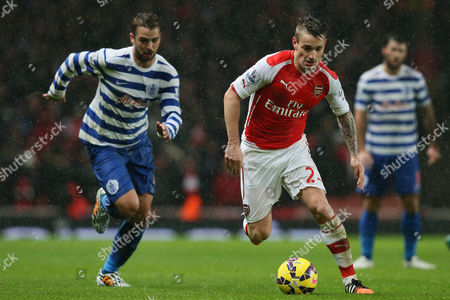 Arsenal's Mathieu Debuchy, right, competes for the ball with Queens Park Rangers' Nico Kranjcar during the English Premier League soccer match between Arsenal and Queens Park Rangers at the Emirates Stadium, London