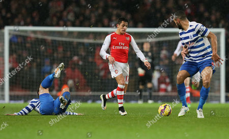 Arsenal's Alexis Sanchez, center, beats Queens Park Rangers' Nico Kranjcar, left, and Steven Caulker to the ball during the English Premier League soccer match between Arsenal and Queens Park Rangers at the Emirates Stadium, London