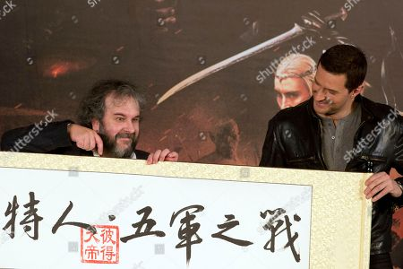 """Peter Jackson, Richard Armitage Director Peter Jackson, left, points at a red stamp with the Chinese words for """"Peter the Great"""" on Chinese calligraphy with the words for """"The Hobbit, The Battle of the Five Armies"""" as actor Richard Armitage looks on during a press conference held in Beijing"""