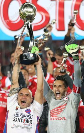 Santa Fe's Omar Perez, left, and Camilo Vargas, right, hold up the Colombian national league championship trophy in celebration, at the end of the Colombian league soccer final game against Deportivo Independiente Medellin in Bogota, Colombia