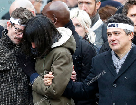 Charlie Hebdo newspaper staff, with editorialist Patrick Pelloux, right, cartoonist Renald Luzier, known as Luz, left, grieve during a rally in Paris. Over a million people, including more than 40 world leaders, streamed into the heart of Paris for a rally of national unity, days after the attacks on the satirical magazine Charlie Hebdo, police officers and a kosher grocery