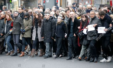 Charlie Hebdo newspaper staff, with cartoonist Renald Luzier, known as Luz, front third left with mustache, march with relatives, right, of Jewish victim of the koscher supermarket, Michel Saada, in Paris, France, . A rally of defiance and sorrow, protected by an unparalleled level of security, on Sunday will honor the 17 victims of three days of bloodshed in Paris that left France on alert for more violence