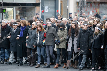 Charlie Hebdo newspaper staff, with cartoonist Renald Luzier, known as Luz, at center with moustache, march in Paris, France, . A rally of defiance and sorrow, protected by an unparalleled level of security, on Sunday will honor the 17 victims of three days of bloodshed in Paris that left France on alert for more violence