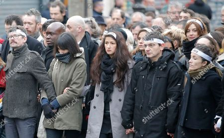 Charlie Hebdo newspaper staff, with cartoonist Renald Luzier, known as Luz, left, march in Paris, France, . A rally of defiance and sorrow, protected by an unparalleled level of security, on Sunday will honor the 17 victims of three days of bloodshed in Paris that left France on alert for more violence