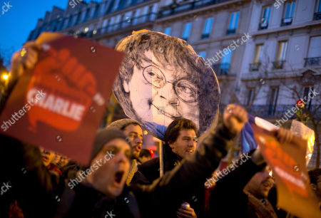 Stock Image of People demonstrate on Republique square with a portrait of slain Charlie Hebdo cartoonist Jean Cabut known as Cabu, during the demonstration in Paris, France, . Hundreds of thousands of people marched through Paris on Sunday in a massive show of unity and defiance in the face of terrorism that killed 17 people in France's bleakest moment in half a century