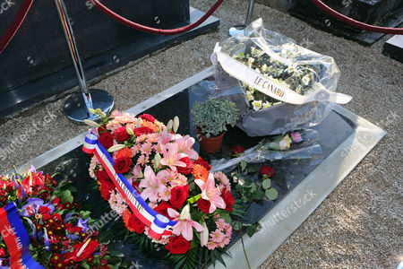Flowers offered by French satirist newspaper Le Canard Enchaine, are laid on the tomb of Charlie Hebdo cartoonist Jean Cabut, known as Cabu, who was buried earlier Wednesday, in the Chalons-en-Champagne cemetery, eastern France, . The core of the irreverent newspaper's staff perished a week ago when gunmen stormed its offices, killing 12 people and igniting three days of bloodshed around Paris. Charlie Hebdo employees who survived the massacre published a new issue of the magazine becoming known as the survivor's issue that appeared on the streets Wednesday with a print run of 3 million, more than 50 times the paper's usual circulation