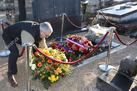 Stock Picture of A man puts flowers on the tomb of Charlie Hebdo cartoonist Jean Cabut, known as Cabu, who was buried earlier Wednesday, in the Chalons-en-Champagne cemetery, eastern France, . The core of the irreverent newspaper's staff perished a week ago when gunmen stormed its offices, killing 12 people and igniting three days of bloodshed around Paris. Charlie Hebdo employees who survived the massacre published a new issue of the magazine becoming known as the survivor's issue that appeared on the streets Wednesday with a print run of 3 million, more than 50 times the paper's usual circulation