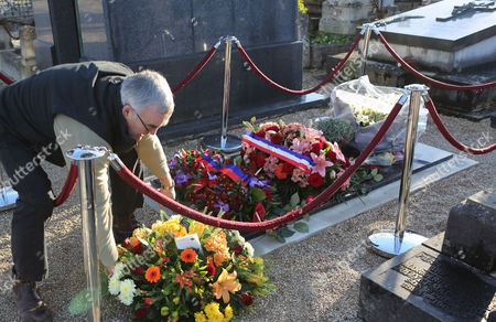 A man puts flowers on the tomb of Charlie Hebdo cartoonist Jean Cabut, known as Cabu, who was buried earlier Wednesday, in the Chalons-en-Champagne cemetery, eastern France, . The core of the irreverent newspaper's staff perished a week ago when gunmen stormed its offices, killing 12 people and igniting three days of bloodshed around Paris. Charlie Hebdo employees who survived the massacre published a new issue of the magazine becoming known as the survivor's issue that appeared on the streets Wednesday with a print run of 3 million, more than 50 times the paper's usual circulation
