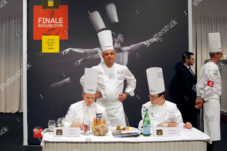 """Jerome Bocuse, the son of Chef Paul Bocuse, center, stands between Honorary President of the Bocuse d'Or Grant Achatz of the USA, left, and President of the international jury Thibaut Ruggeri of France, right, as they taste a dish during the """"Bocuse d'Or"""" (Golden Bocuse) trophy, at the 15th World Cuisine contest, in Lyon, central France, . The contest, a sort of world cup of the cuisine, was started in 1987 by Lyon chef Paul Bocuse to reward young international culinary talents"""